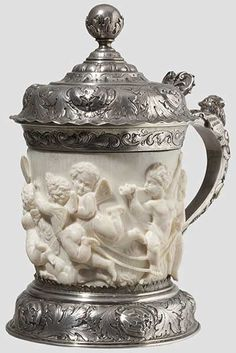 A silver-mounted ivory tankard                                    Historism period in the style of the 17th century Carved ivory body displaying a reclining maid and playing putti in high relief.