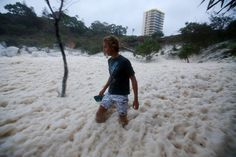 Wild weather in the Australian state of Queensland has led to a small town becoming covered in foam whipped up by rough seas.