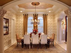 Elegant Bronze hues from the ceiling, wallpaper and draperies emit a calming, yet formal atmosphere. An orange and red floral centerpiece brings in familiar fall colors that pop within the room.