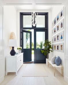 Gorgeous black front doors accented with glass panels and fitted beneath large transom windows are illuminated by a white chandelier hung over a beige rug. Double Glass Doors, Glass Barn Doors, Glass Panel Door, Glass Front Door, Front Door Decor, Glass Panels, Door Entryway, Entry Foyer, Entryway Tables
