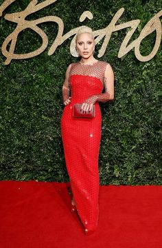 Lady Gaga wears a red Tom Ford dress with platforms