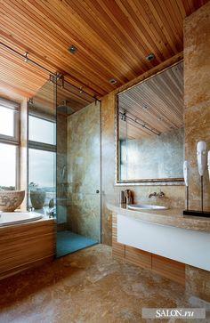 В интерьере использованы только натуральные отделочные материалы. Светлая, с большим окном ванная комната хозяев облицована травертином. Благодаря его золотисто–бежевому тону она всегда выглядит тёплой