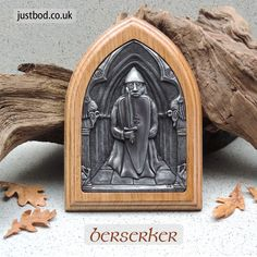 Berserker - a handcrafted solid oak wall plaque with an inlaid design cold cast in bronze or aluminium from an original sculpture by bod. Featuring a figure based on one of the 'Berserker' rooks from the Lewis Chessmen. #Berserker #Viking #LewisChessmen #Chess #VikingArt #WallPlaque