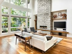 There is a simple yet classy off-white sofa resting in front of a wide flat screen TV. The floor is finished with glossy parquet wood, and there are a few wood accents on the shelves, display desk and center table.