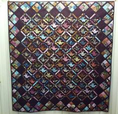 """""""The quilt pattern is by Margaret Rolfe. I started it several years ago, and finally finished after many fits and starts. Each bird is paperpieced. There are 2,501 pieces in the top. All of the birds were made from oriental fabrics."""" -- Bonnie Sawyer-Banda  We believe this is Margaret Rolfe's """"Peace Quilt"""".  The center of each block is an origami crane which has come to be a symbol of peace and healing."""