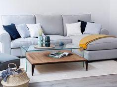 Sofá gris, mesa de centro en cristal, combinada con mesa en madera