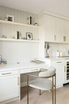 A separate office wasn't in the works for the homeowners, but they found a solution: a kitchen desk niche. It's just right off the main kitchen area and matches with the rest of the white cabinetry. Bold, patterned wallpaper gives the desk a sense of separation from the rest of the kitchen, too.