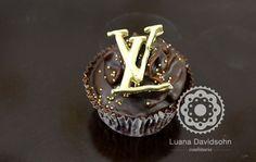 Cupcake de chocolate com doce de leite e casquinha de chocolate, decorado com bolinhas douradas e a logomarca da Louis Vuitton em pasta americana dourada. A logomarca pode decorar cupcakes e bolos, além de vários outros doces e vai deixar sua mesa de doces um luxo!