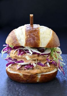 This BBQ Bang Bang Burger is stacked high with crisp slaw and covered with bbq bang bang sauce!
