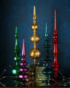 Five Colored Glass Finials at Horchow. I love the colors of these and they would be beautiful on a fireplace mantle.