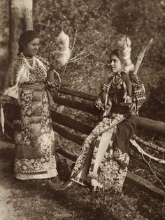 Teenage girls in ornate embroidered dress spin flax fiber for thread.  Location:Roumania.