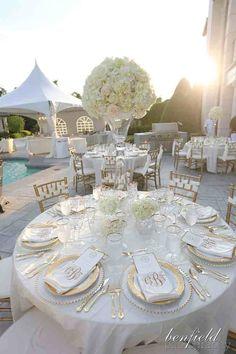 Decoración de mesa en blanco y dorado en una boda al aire libre