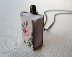 Tiny little floral covered book necklace.