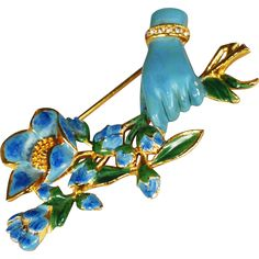 This pretty Victorian revival Coro brooch features a hand holding a stemmed floral bouquet; gold tone metal setting. The light blue enameled hand,