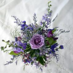 A single, large, open purple rose forms the center of this exotic looking wedding bouquet. Other blue and purple fillers add to the beauty. A pretty option for a bride who fancies blue tones for her wedding.