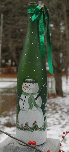 Hand painted wine bottle with fat little snowman - with a crown of holly and surrounded by evergreen trees.  Tied off with some sparkly ribbon and finished off with a little vintage looking jingle ball.  The whole bottle is sparkly, too, had to see in pics and it comes with lights inside, too!