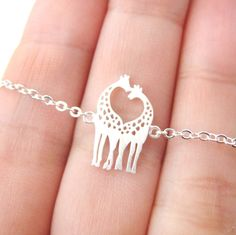 - Details - Sizing - Shipping A simple necklace featuring a pretty charm in the shape of two giraffes facing each other in silver. It is made to look like the giraffes are kissing each other! Super cu