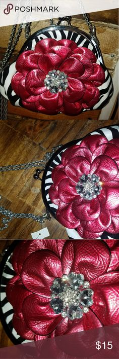 "Zebra Bling Red Flower Evening Purse NWT New Zebra clutch or shoulder bag. Approx 8"" "" 6"" with long silver detachable chain straps.  Very trendy. The attached Red flower is blinged up with some rhinestones.  Inside has 2 small pockets, one with a zipper.  Back side has a zipper pocket as well.  Original paper is still inside. unknown Bags Clutches & Wristlets"