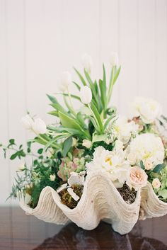 For a seaside wedding gorgeous giant seashells hold floral centerpieces