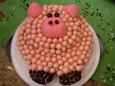 Pig cake: pink frosting, pink malt balls, pink snowballs, pink necco's, junior mints, & m's for the pig eyes and feet.