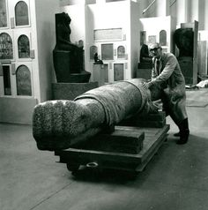 Ray Pierce pushing red granite left arm from a colossal figure of a king, Egyptian Sculpture Gallery, 1976.