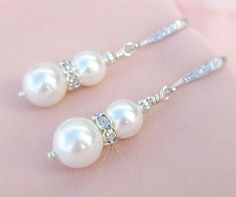 These modern bridal earrings are crafted using top quality soft white glass pearls with a silver toned rondelle of cut crystal sandwiched in between. Stunning classic wedding earrings. Our pearl quali