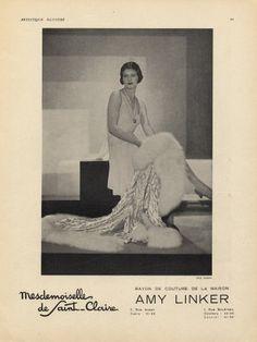 Mademoiselle de Saint-Claire 1930. C'est une publicité pour une maison de couture. Dessus on voit une femme maquillée, cheveux assez courts, féminine. Elle porte une robe blanche qui arrive aux genoux et tient un manteau avec de la fourrure dans ses mains.