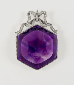 Given by by the Emperor Nicholas II and Empress Alexandra Feodorovna of Russia  to Queen Mary when Princess of Wales on their visit to Cowes, Isle of Wight, August 1909 An amethyst and silver pendant jewel with a large single full cut stone set in an open mount with a jewelled ribbon bow above.