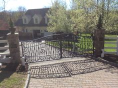 Iron Driveway Gates with custom stone pillars and paver detail on drive.