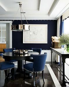 Gorgeous navy blue dining room with blue paint color and white tray dining room ceiling. Polished nickel pendant chandelier over lack round pedestal table surrounded by blue dining chairs with silver nailhead trim. Polished black marble tile dining room floor, black dining console table and floor to ceiling ivory. ➤ Discover the season's newest designs and inspirations. Visit us at  www.moderndiningtables.net #diningtables #homedecorideas #diningroomideas @ModDiningTables