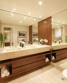 Sofisticação e requinte nesse banheiro com nicho para toalhas madeira, espelho e iluminação top.