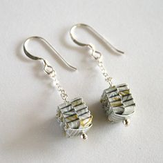 Gold and silver folded Japanese paper hangs from sterling silver chains and hooks to create a dangling pair of fashionable earrings! These hang