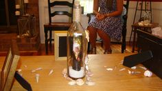 Message in a bottle! Clearance bottle from big lots, sand and seashells from the dollar store. Roll up a 4x6 picture and slide it in. Use pencils and double sided tape to move around and open up.