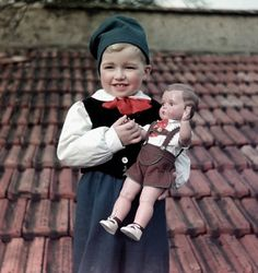 A boy, age 4, poses with his composition doll (with traditional lederhosen), maker unknown, Germany, 1949.