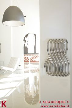 """ARABESQUE  Design and technology come together in this radiator designed by the renowned designer Ron Arad.  Arabesque was created by the movement of a double ellipse tubular steel that winds poetically to create a series of """"8"""" winding shapes.  It can be used both vertically and horizontally, becoming also a handy towel rail."""