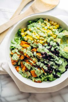 This healthy Spicy Southwestern Salad recipe has roasted sweet potatoes, black beans, corn, lettuce, and creamy avocado dressing! 315 calories.