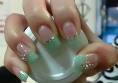 Interesting, unique, light teal color nails with pink accent crystals.