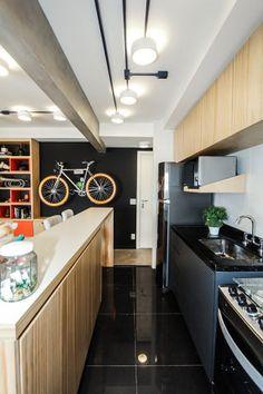 Sofá de pallets, aparador de caixotes de plástico e suporte na parede para a bike dão um toque moderno ao décor, mas sem gastar muito
