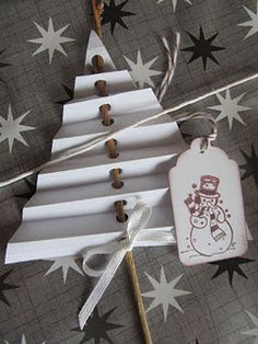 Made with a twig & paper (cut in a triangle & folded acordian style). Punch a hole in the middle of the paper while it is still folded, then thread the stick through. Add ribbon & tag... can be used to embellish gifts or just as a decorative element.