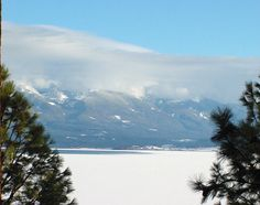 This is winter on Flathead Lake near Polson, Montana. The lake freezes over just enough to do some ice fishing most years. I loved the composition here, with the two pine trees framing the lake and the snow covered Mission Mountains shrouded in clouds.    Western Montana is such a beautiful place, no matter what the season. I still have my real estate brokers license there and help people hook up with the best REALTORS in that part of the world!