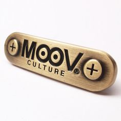 Metal decal with bendable rear prongs.  Brushed Antique Brass finish.
