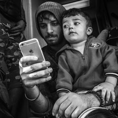 This father and son were taking selfies and playing games on a gold iPhone on the steps of a train in Tovarnik Croatia. #refugeecrisis for @TIME by patrickwitty