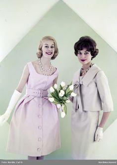 Modell i rosa klänning, vita handskar och halsband med vita tulpaner i handen bredvid modell i grå klänning och jacka, halsband och vita handskar. Fotograf: Carl A Nordin, ca 1960-1965