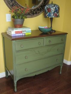 Dark olive/army green with a glaze, dark stained top, very faint distressed, cut glass knobs, by European Paint Finishes