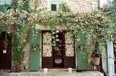 Love the vines against white rock and green shutters