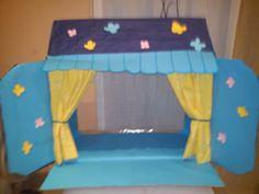 un escenario para marionetas casero hecho con un acaja de cartón, una tela, flores de papel y folios pintados.