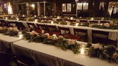 Mixed foliage garlands with protea, sunflowers, dinner plate dahlias and accent flowers from Seasonal Celebrations line the guest tables with jute banded Mason jars add the romance of candlelight to this outdoor reception.