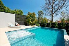 jardín con jacuzzi y piscina con fondo de mosaico