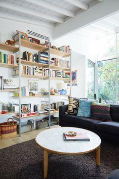 dark sofa + rug, light walls + coffee table + shelving