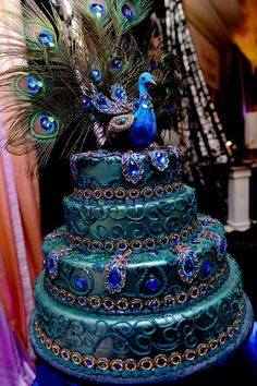 How beautifully exotic! A peacock inspired cake.....I(Staci) would have this pro made,b/c it would be a mess by the time I got done with it...lol.
